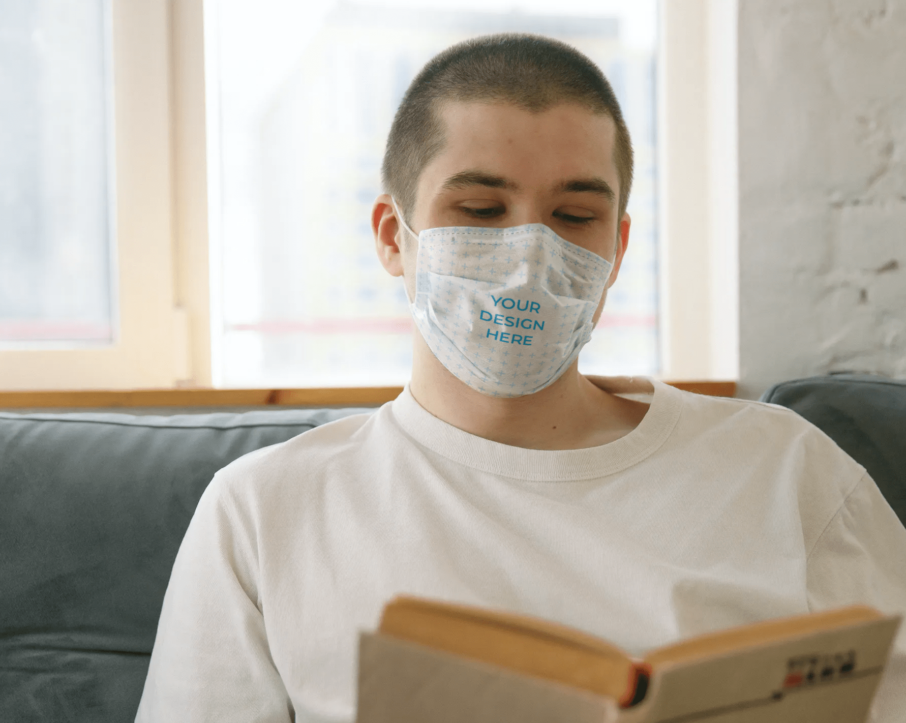 Man Wearing a Face Mask Reading a Book Free Mockup Generator