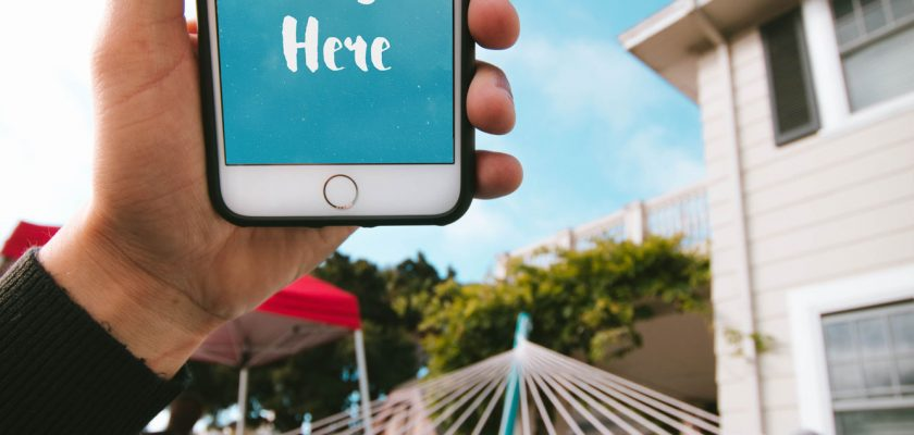 iPhone in the Hand of a Guy in a Hammock Free PSD Mockup
